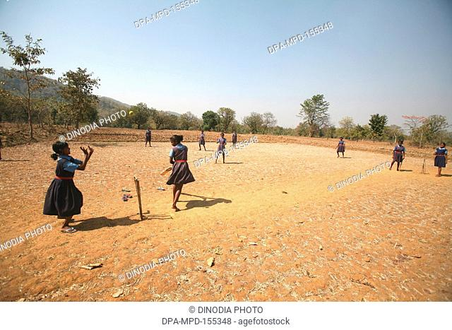 School girls in uniform playing cricket in dry fields in Jharkhand ; India