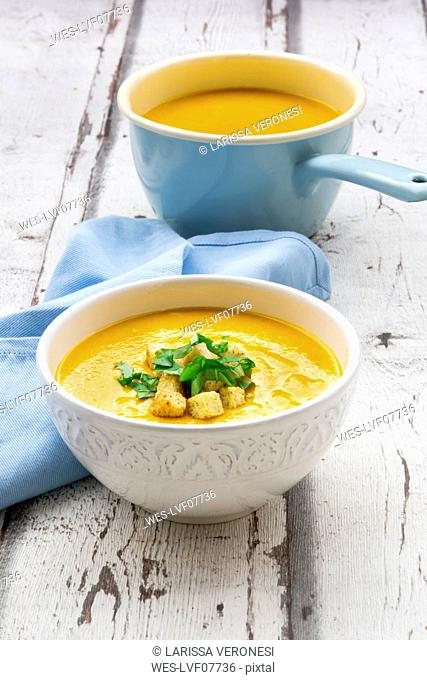 Bowl of sweet potato soup with mango, curcuma and coconut milk, croutons and basil