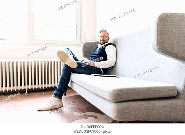 Businessman with laptop, relaxing on coach