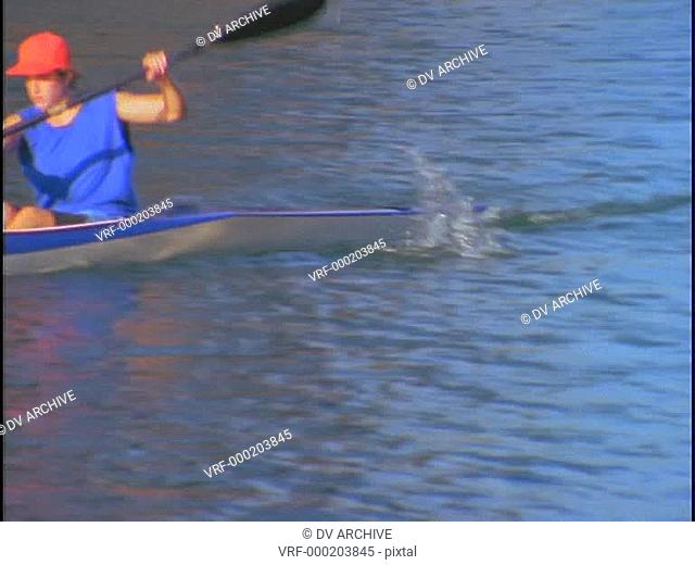 A woman kayaker rows quickly through the water