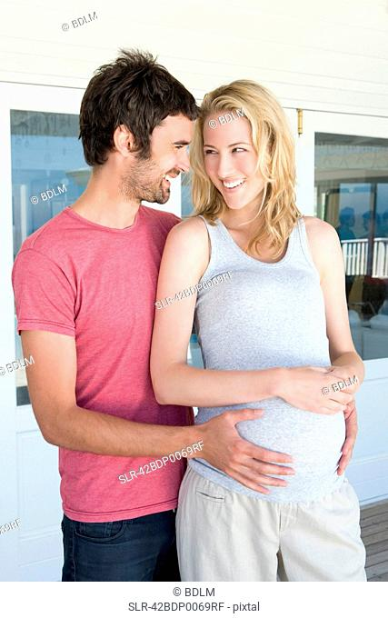 Man holding pregnant girlfriends belly
