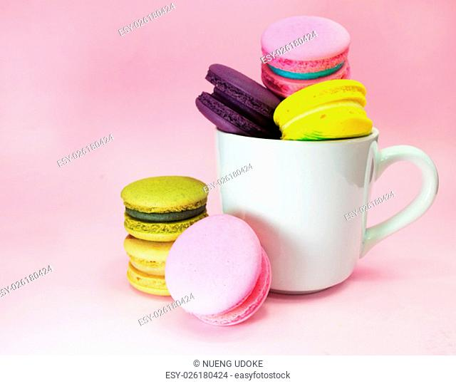 macarons in cup on pink background
