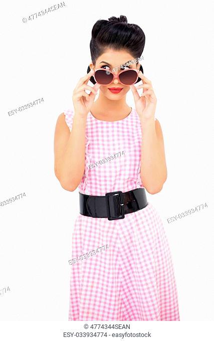 Lovely black hair model looking over her sunglasses on white background