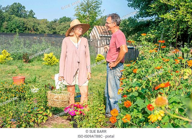 Male and female farmers chatting in garden