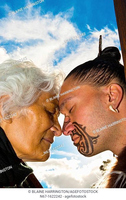A Maori man with ta moko facial tattoo and an elderly Maori woman doing hongi traditional Maori greeting , Te Puia New Zealand Maori Arts & Crafts Institute