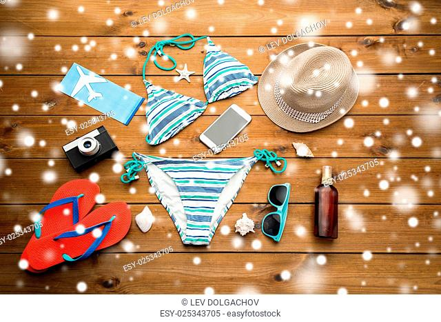 vacation, travel, tourism and winter holidays concept - smartphone, camera and beach stuff over snow