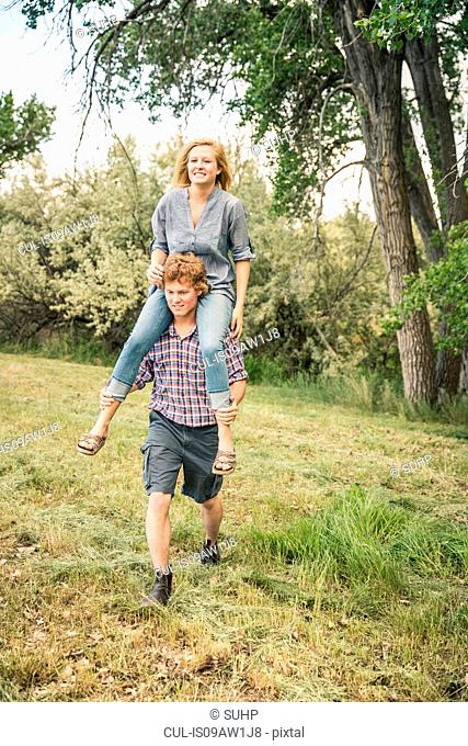 Young man carrying teenage girl on shoulders in rural field