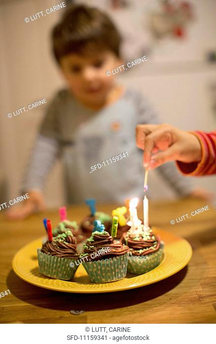 Candles being lit on birthday cupcakes