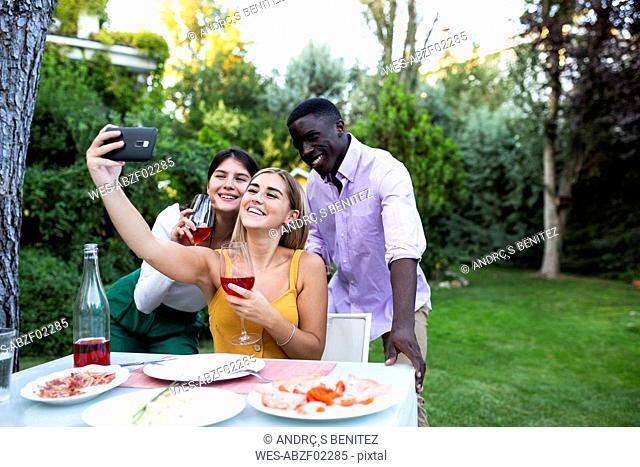 Friends having fun at a summer dinner in the garden, taking selfies