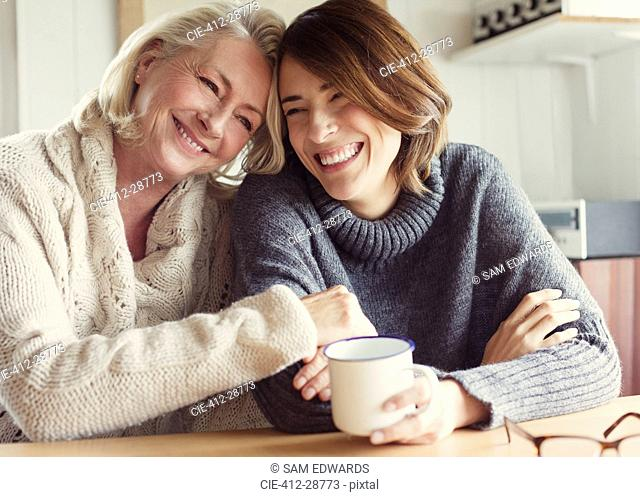 Laughing mother and daughter in sweaters hugging and drinking coffee
