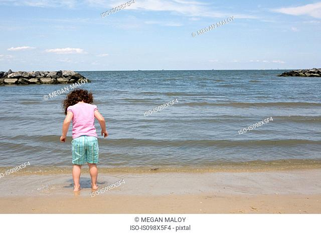 Young girl paddling at water's edge