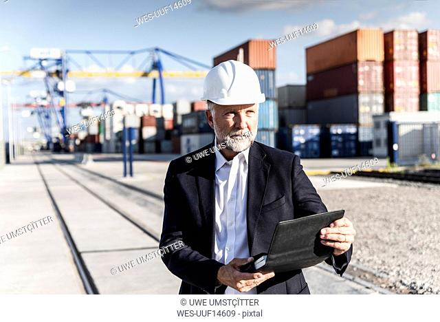 Businessman at cargo harbour, wearing safety helmet, using smartphone