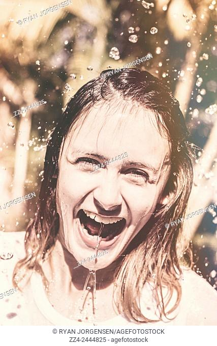 Cute travel portrait of a pretty girl laughing in the downfall of falling water. Playing in the rain