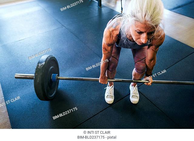 Caucasian women lifting barbell in gymnasium