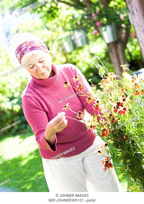 A woman pottering in her garden
