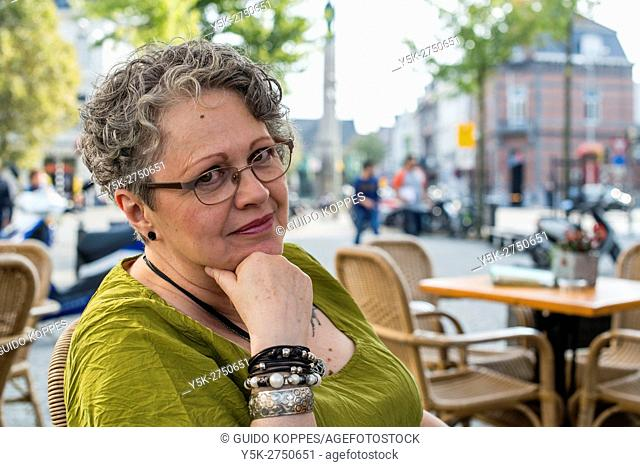 Maastricht, Netherlands. Elder woman having a conversation while sitting on a terrace
