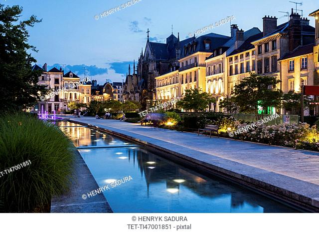 France, Grand Est, Troyes, Promenade along canal with illuminated buildings in background
