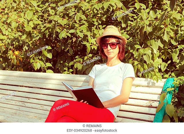 Beautiful girl hipster sits with a book on a bench in the summer