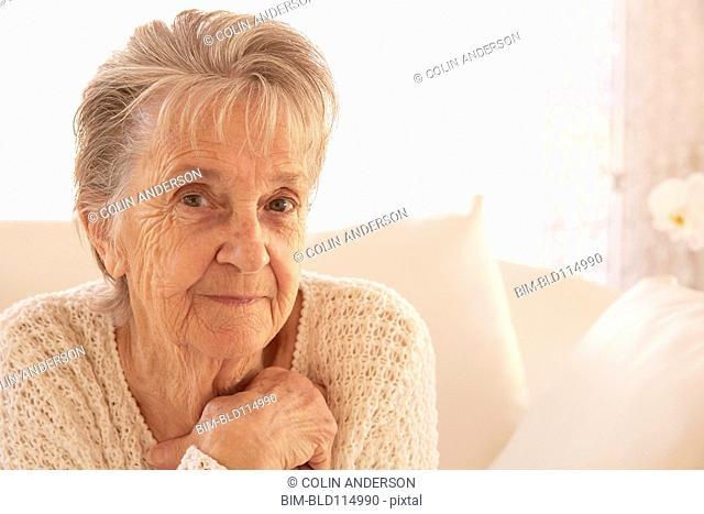 Older Caucasian woman smiling on sofa