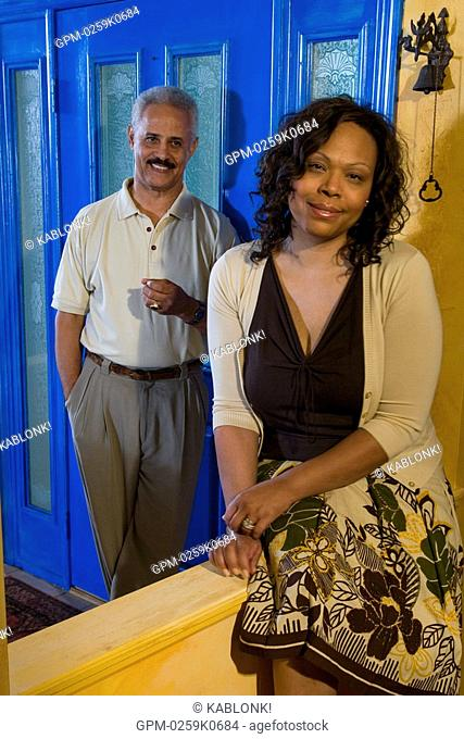 Portrait of mature African American couple near doorway of home, looking at camera