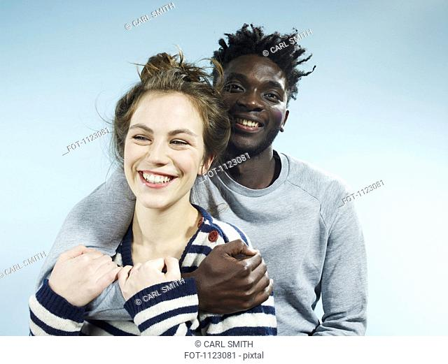 A smiling young man embracing his smiling girlfriend from behind