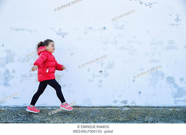 Little girl walking in front of a wall