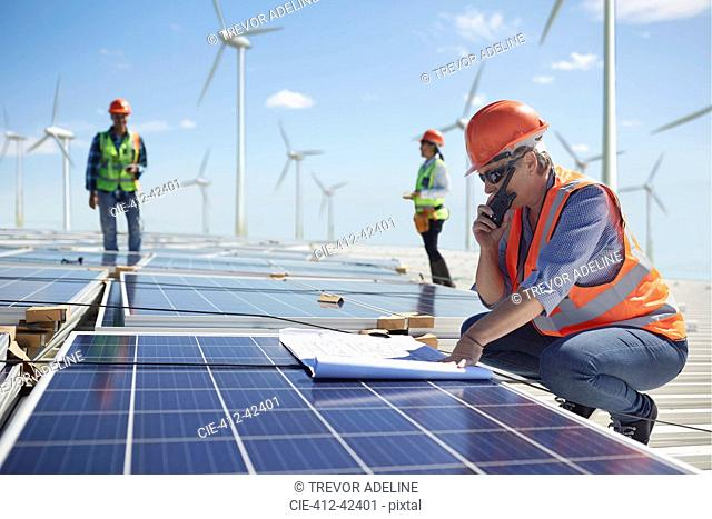 Engineer with walkie-talkie and blueprint at solar panel at sunny power plant