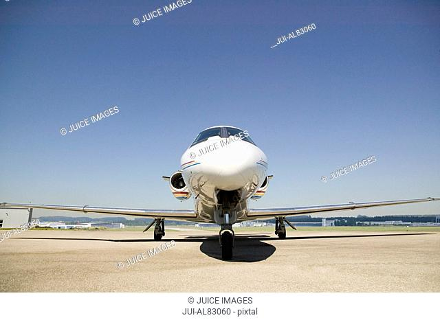 Front view of airplane on tarmac under blue sky