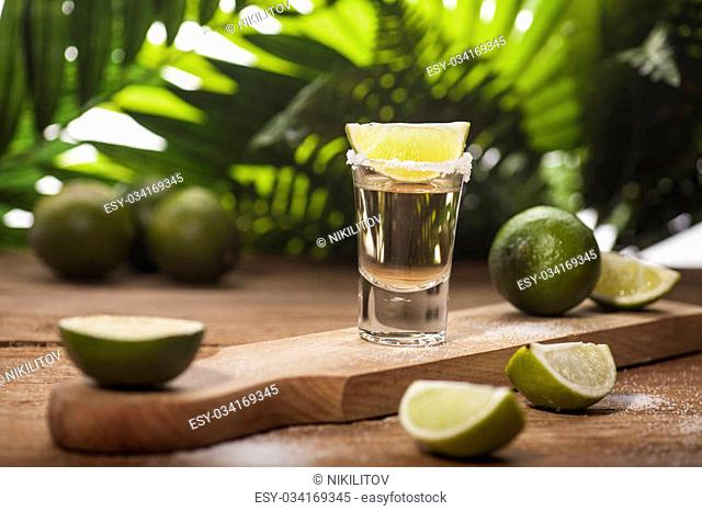 Gold tequila shot with lime fruits on wooden and green tropical leaves background