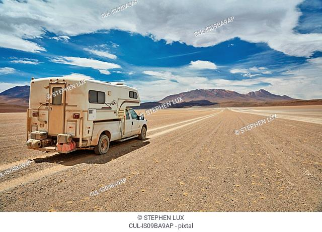 Recreational vehicle, travelling across landscape, rear view, Villa Alota, Potosi, Bolivia, South America