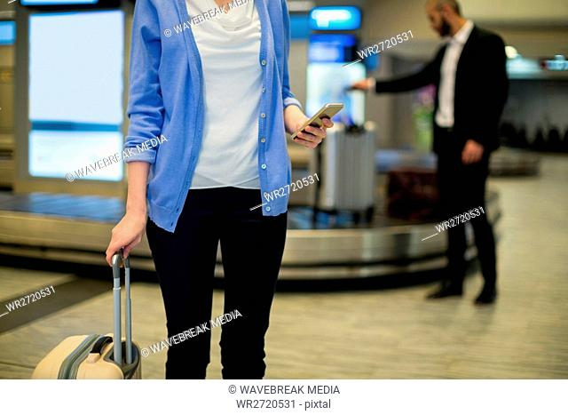 Mid section of businesswoman standing with luggage using mobile phone in waiting area