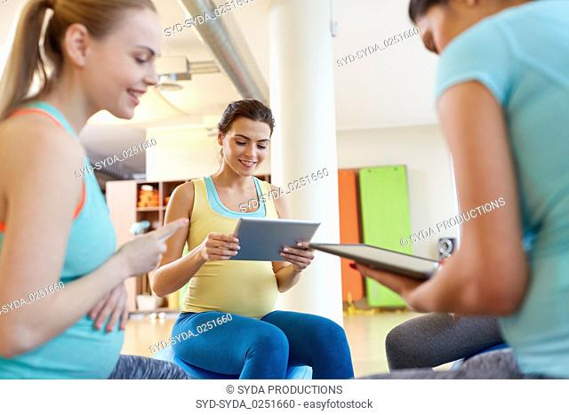 happy pregnant women with tablet pc in gym