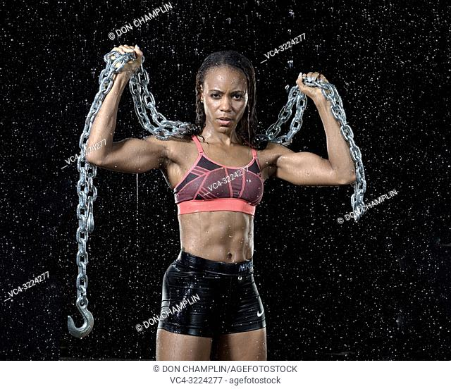 Black, female athlete raising chain in rain