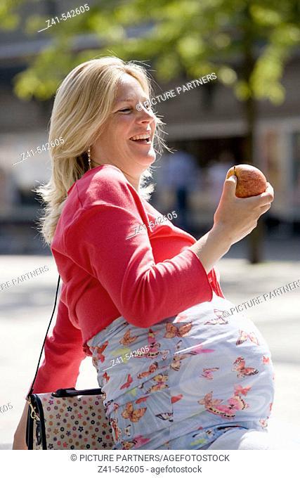 Pregant woman is enjoying eating an apple