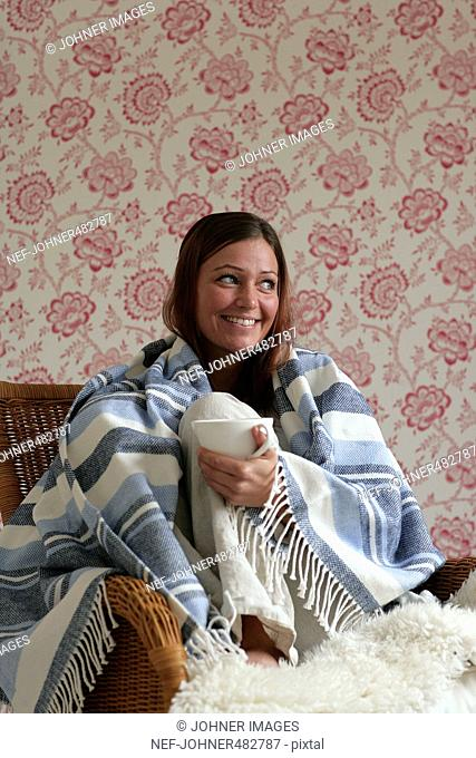Scandinavian woman with a cup of coffee sitting with a blanket wrapped around her