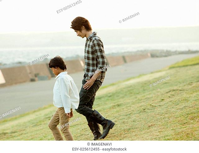 Father and son walking on the grass