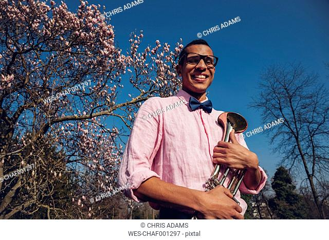 Young man in park in spring, wearing bow tie, holding trumpet