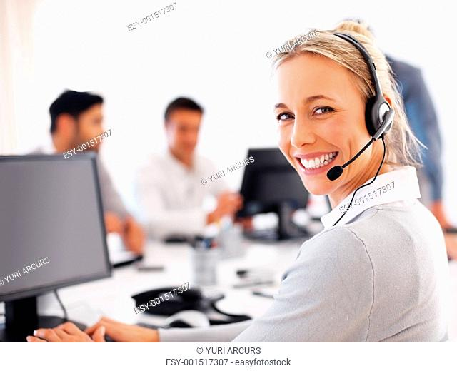 Beautiful female customer service executive working on computer and smiling at you