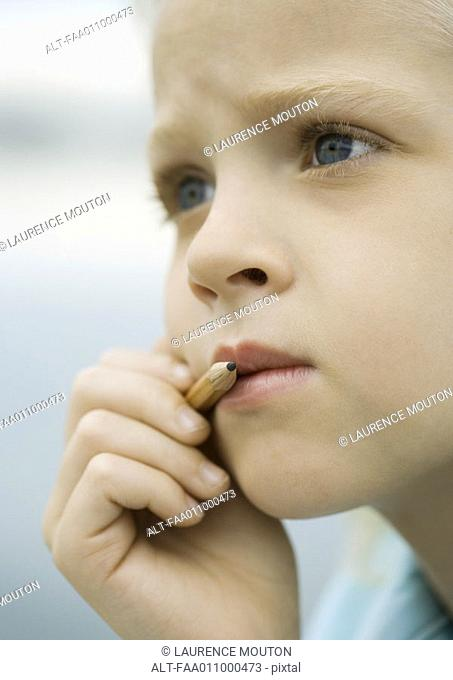 Girl holding pencil next to mouth