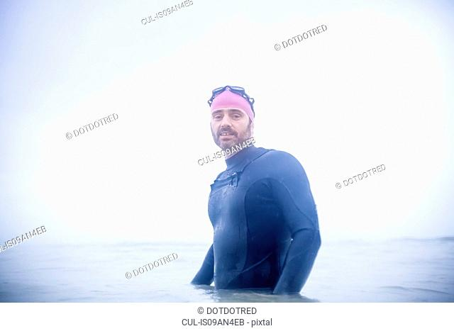 Portrait of mature man standing waist deep in the sea
