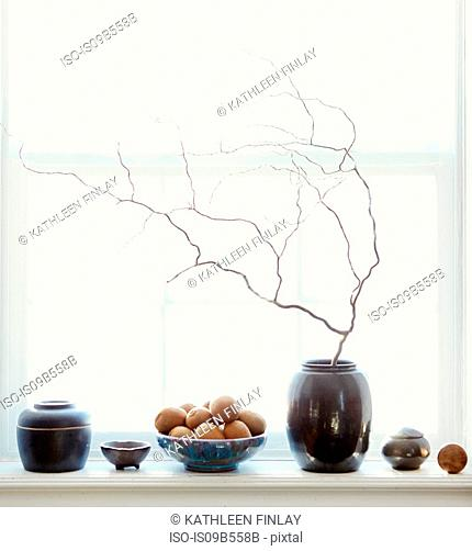 Composition of fruits and vases by window