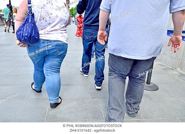Two unidentified overweight / obese people walking along the South Bank, London, England, UK