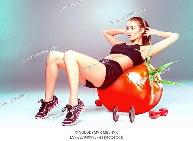 Sporty woman doing aerobic exercise on a tomato as fitness ball. Concept of diet and healthy foods and lifestile