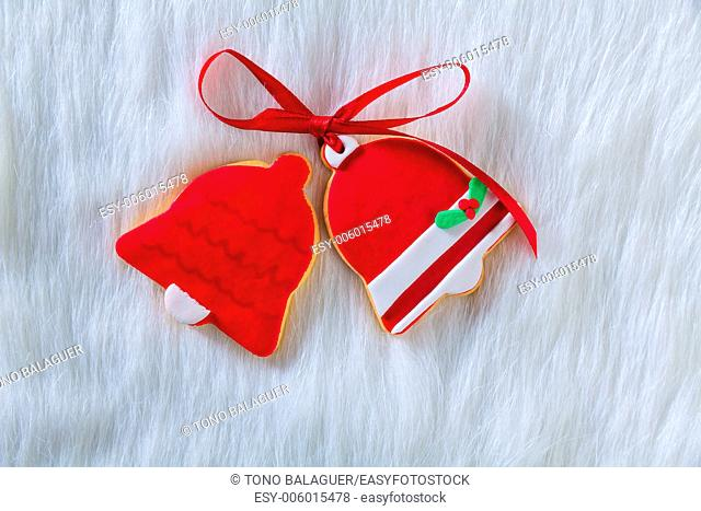 Christmas cookies Xmas red bell shape and ribbon on white fur background