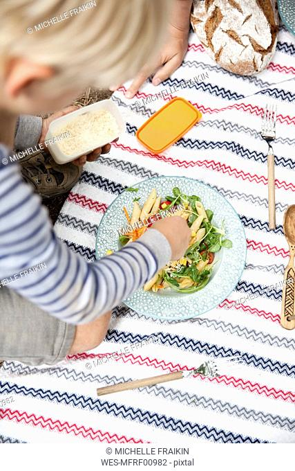 Boy dispersing grated cheese on pasta salad during a picnic in forest