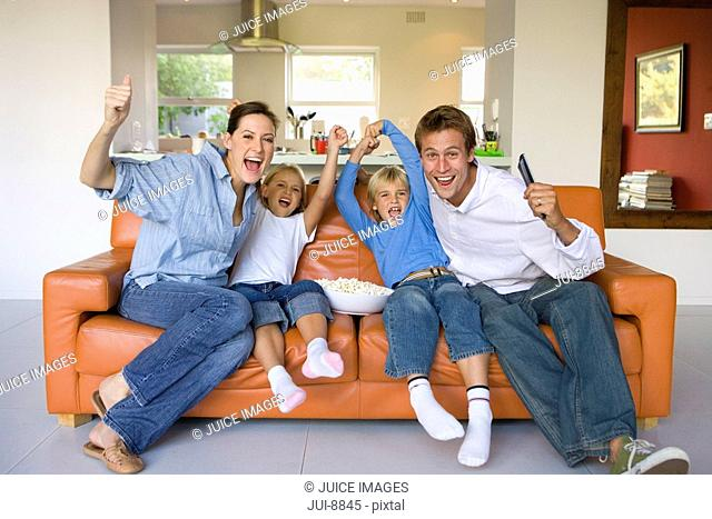 Family of four sitting on sofa in living room, cheering, portrait