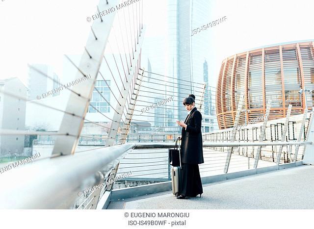 Businesswoman with trolley luggage on pedestrian bridge, Milan, Italy