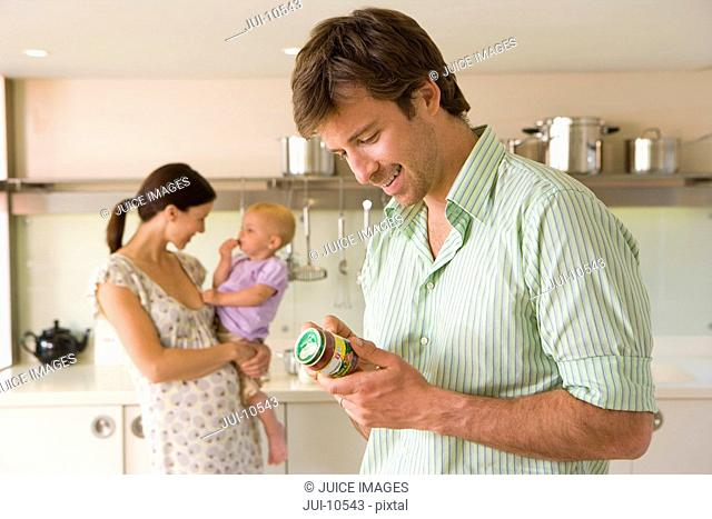 Young couple in kitchen, pregnant woman with baby girl 6-9 months, man looking at baby food label