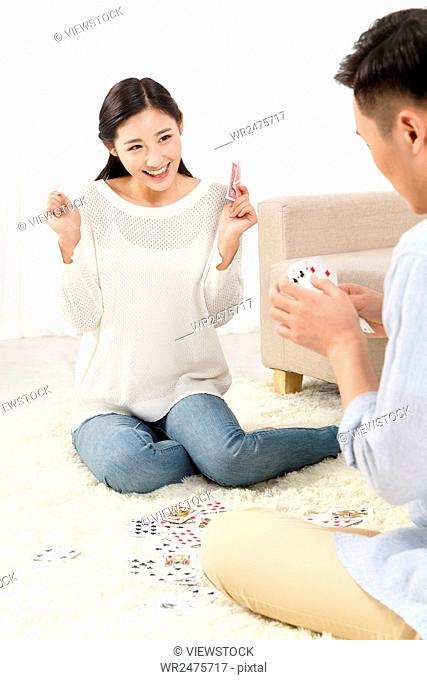 Young lovers playing cards