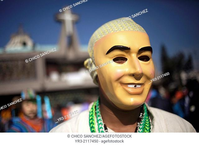 A dancer wearing a smiling masks from Los Altos, Veracruz, get ready to perform the Danza de San Juan at the pilgrimage to Our Lady of Guadalupe Basilica in...